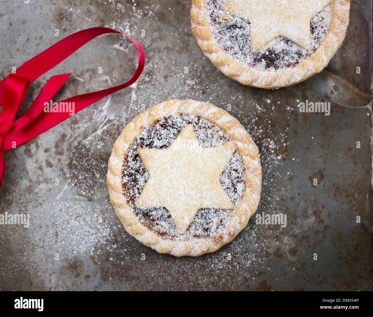 Home made icing sugar dusted mince pies on grey rustic surface with red ribbon - Stock Image