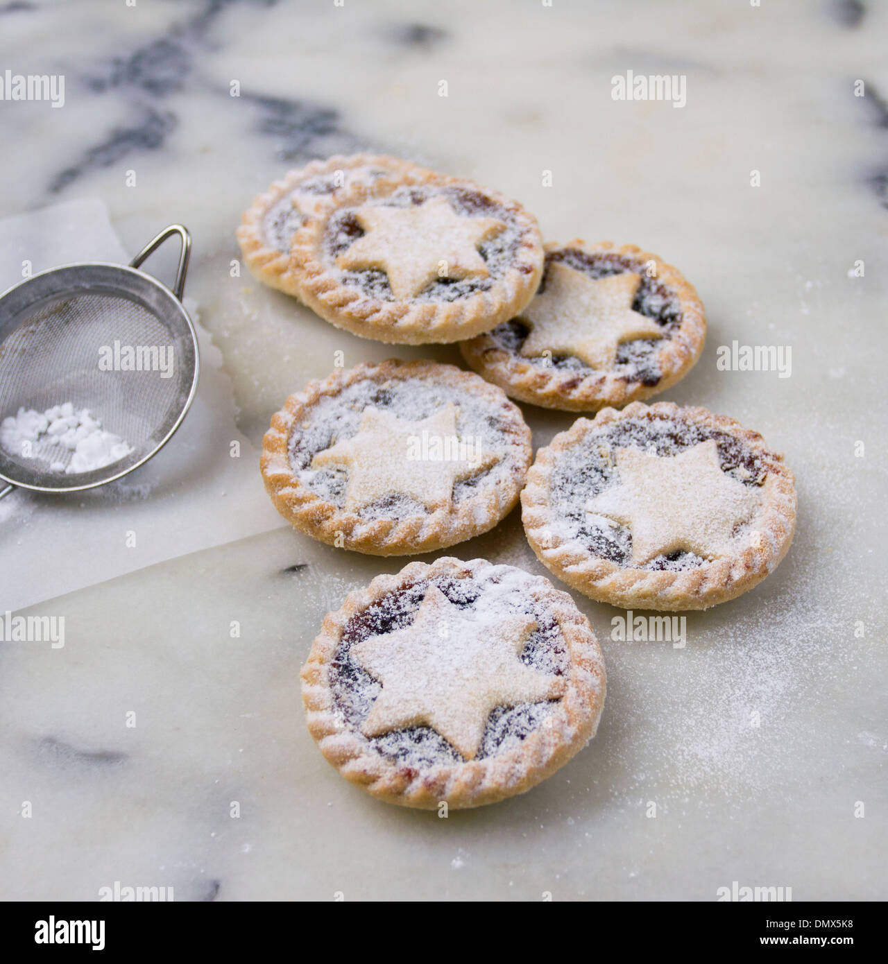 Home made icing sugar dusted mince pies on a grey marble surface - Stock Image