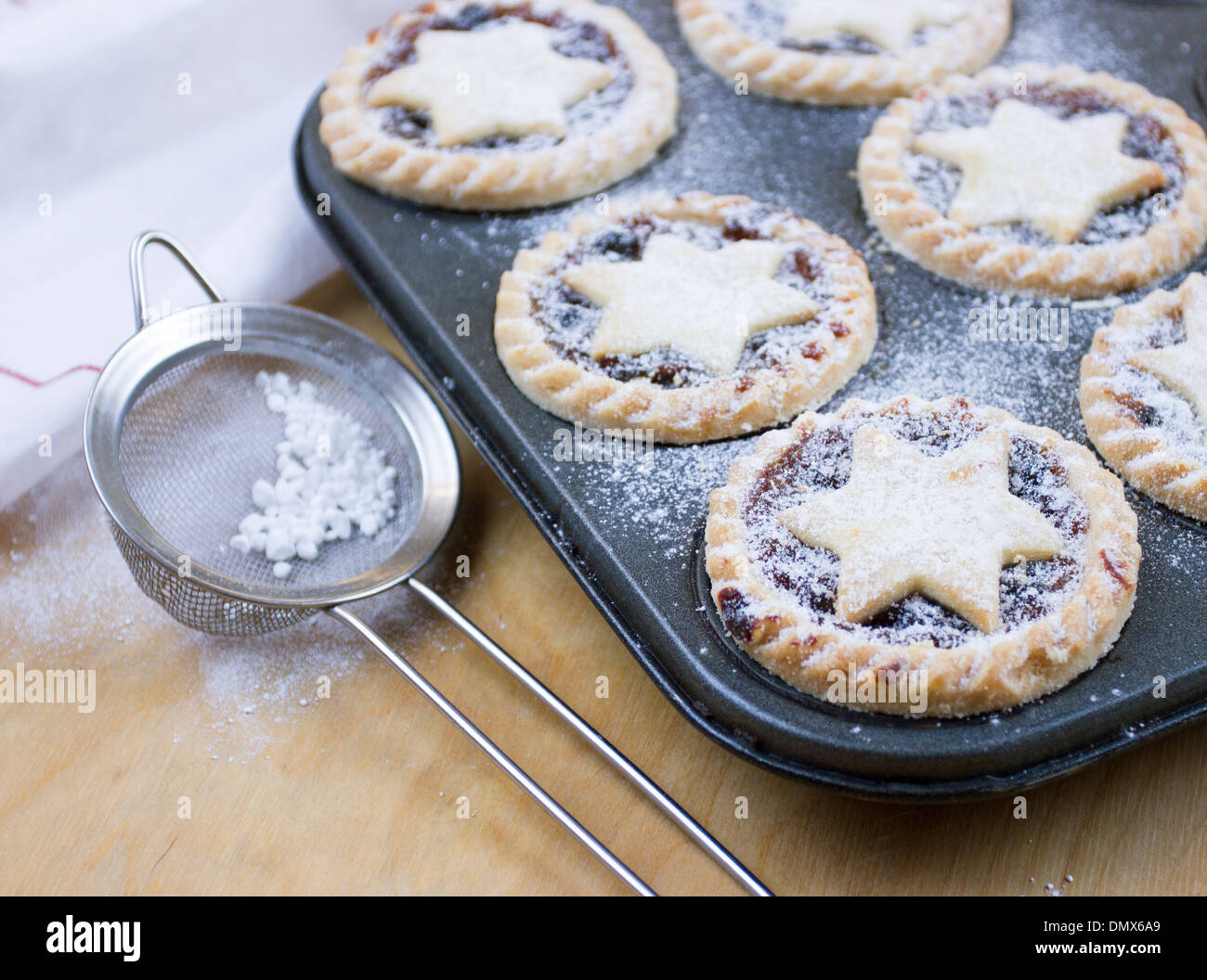 Home made icing sugar dusted mince pies in baking tray - Stock Image