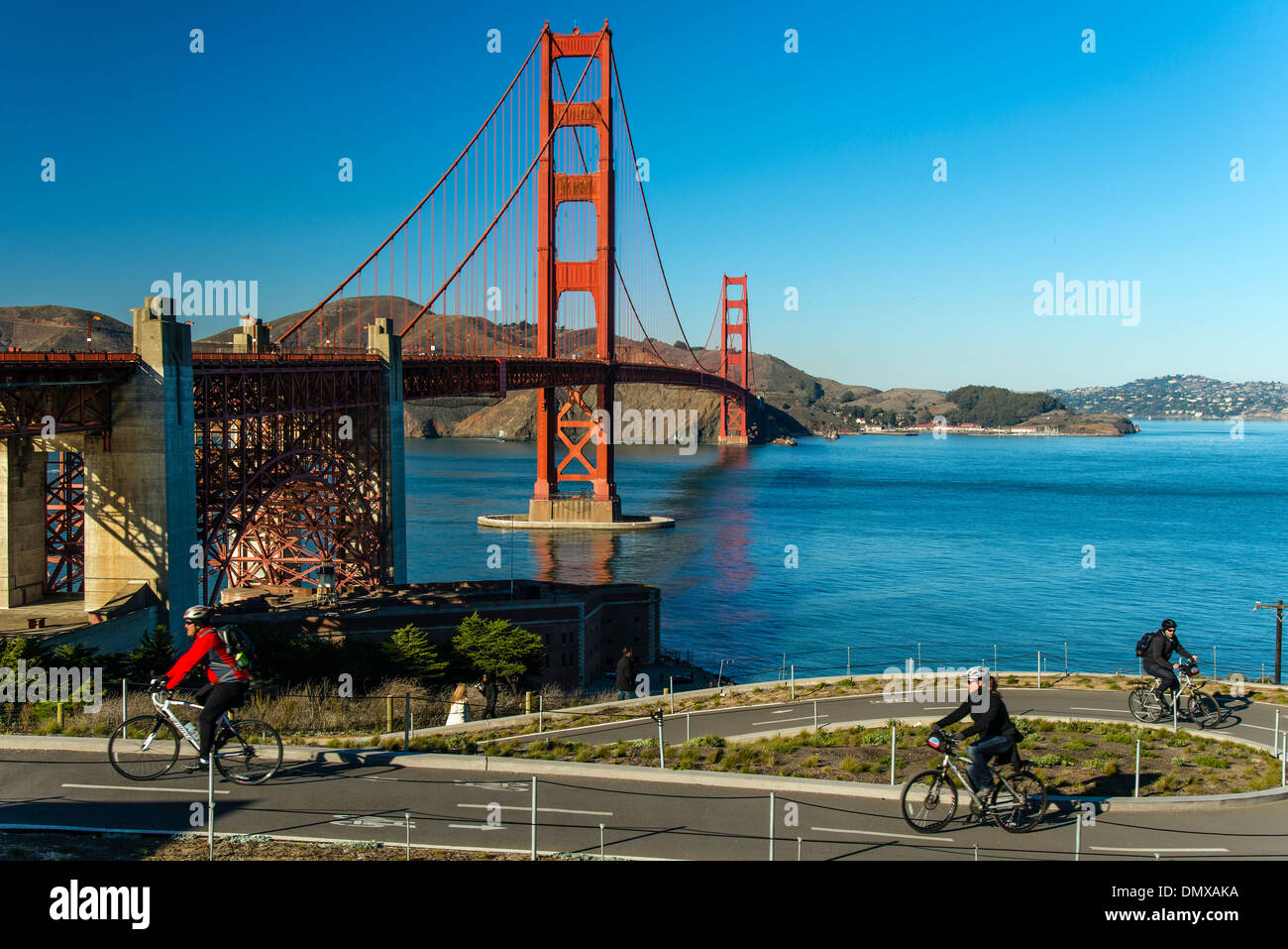Cyclists riding on a bike lane with Golden gate suspension bridge behind, San Francisco, California, USA - Stock Image