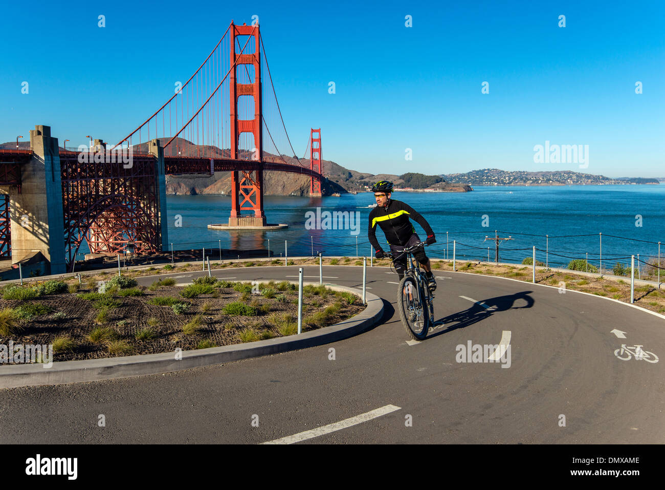 Cyclist riding his mountain bike on a bike lane with Golden gate suspension bridge behind, San Francisco, California, USA - Stock Image