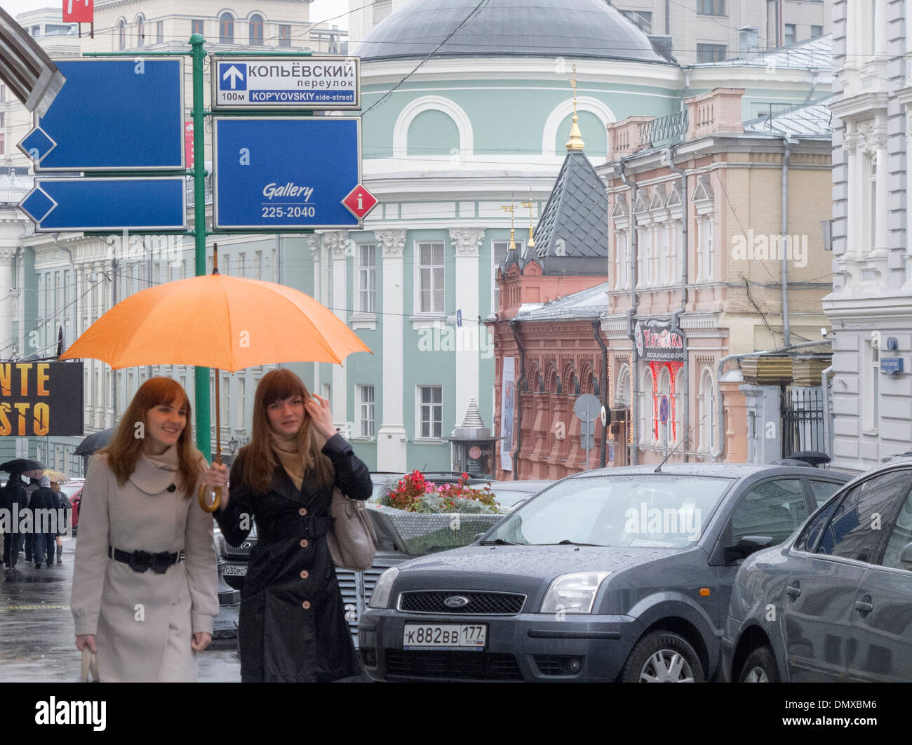 Two young ladies walk sheltered from the rain in Moscow with an orange umbrella. - Stock Image