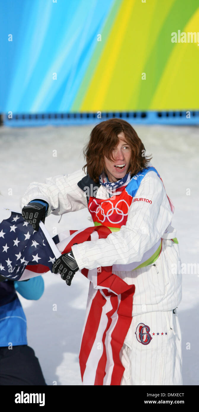 Feb 12, 2006; Bardonecchia, ITALY; The men's snowboard halfpipe competition was held at Bardonecchia Sunday. Former Duluth resident Mason Agguire was shut out of a medal, placing fourth. His teammates, Shaun White and Daniel Kass won gold and silver, respectively. Pictured: Shaun White prepared to drape himself in the American flag after he picked up a gold medal in the halfpipe Su - Stock Image