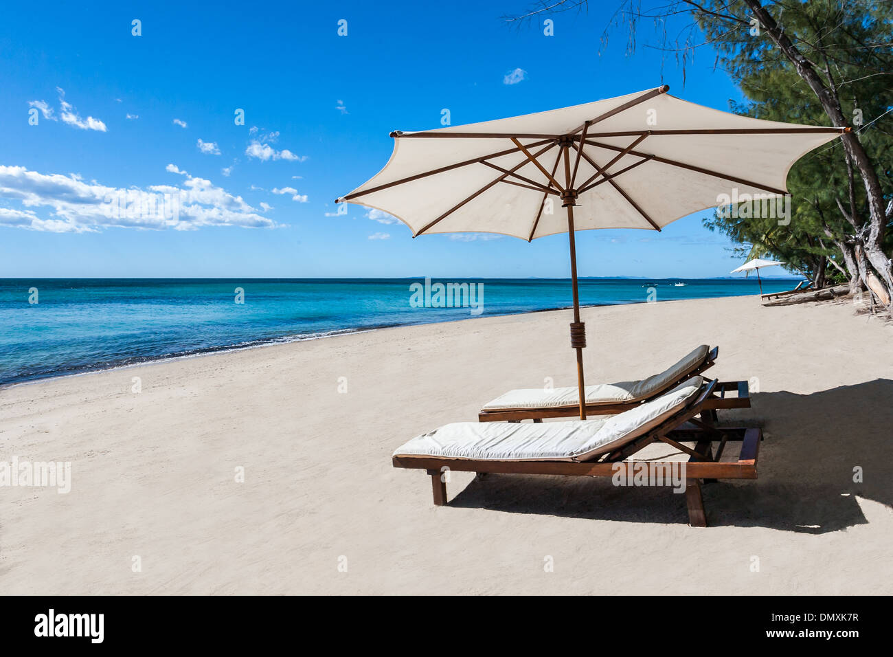 Sunbed and umbrella on a beautiful tropical beach - Stock Image