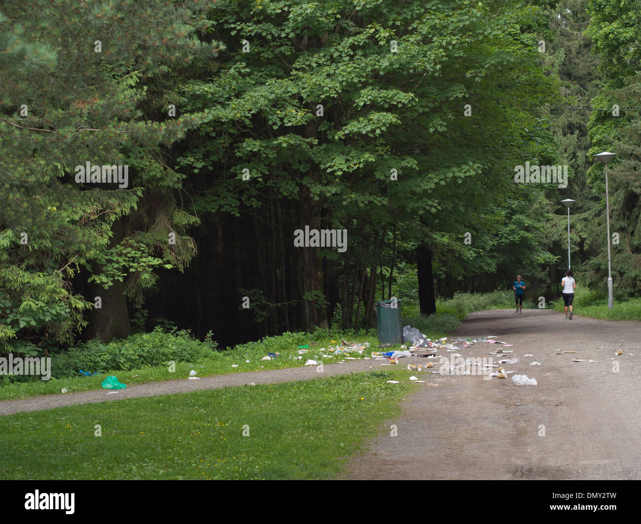 Park or woodland area with footpaths, wastepaper and other garbage polluting the area around a bin, two joggers, Oslo Norway - Stock Image