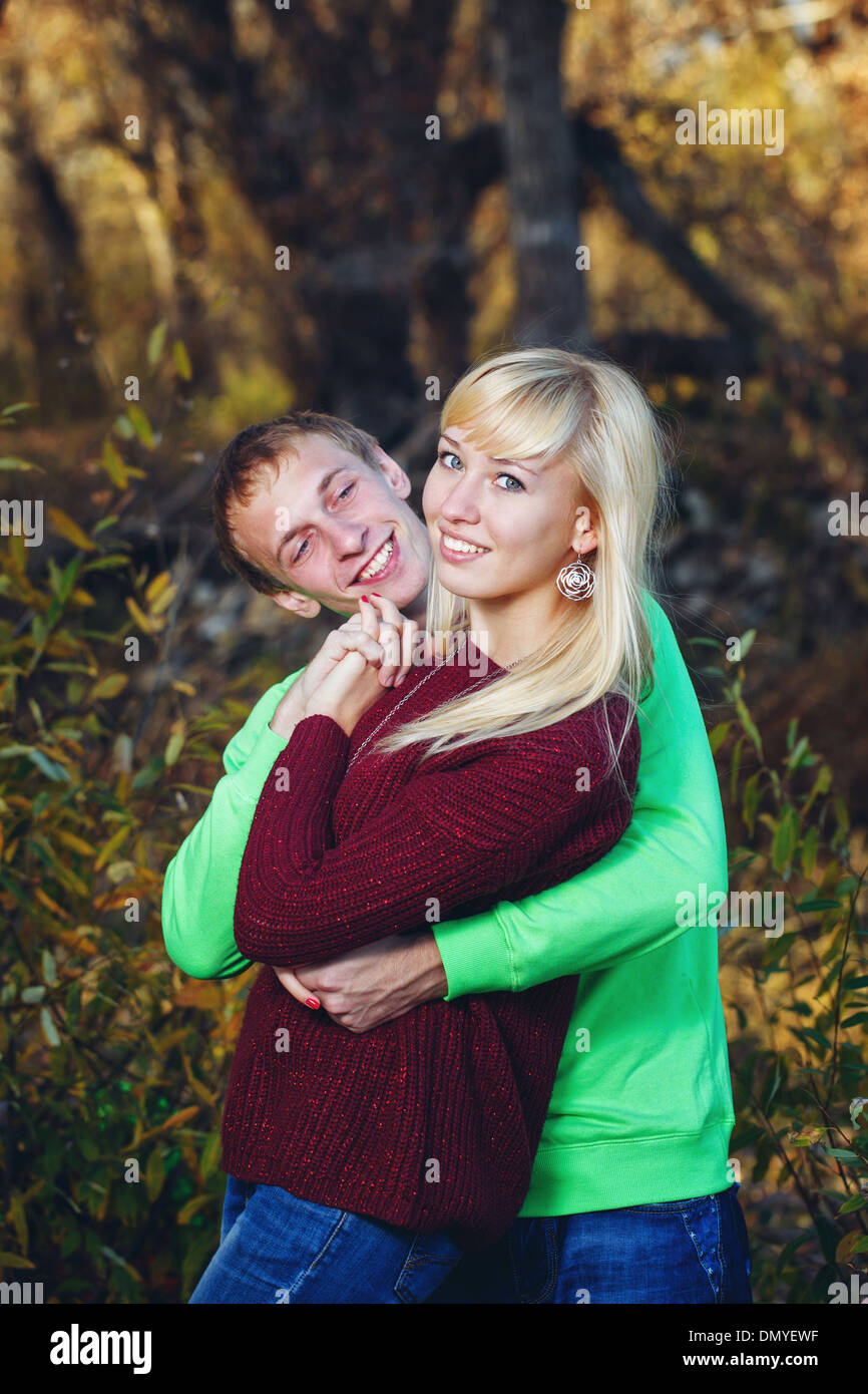 Young couple tenderly and lovingly embrace each other in autumn park - Stock Image