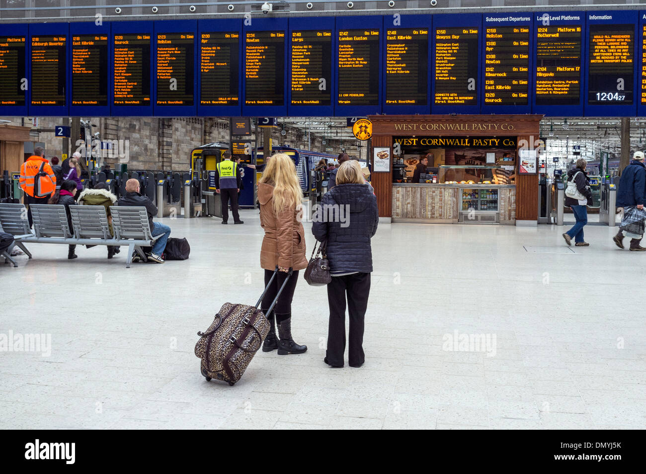 Two women passengers looking at the destination board at Glasgow Central railway station, Glasgow, Scotland, UK - Stock Image