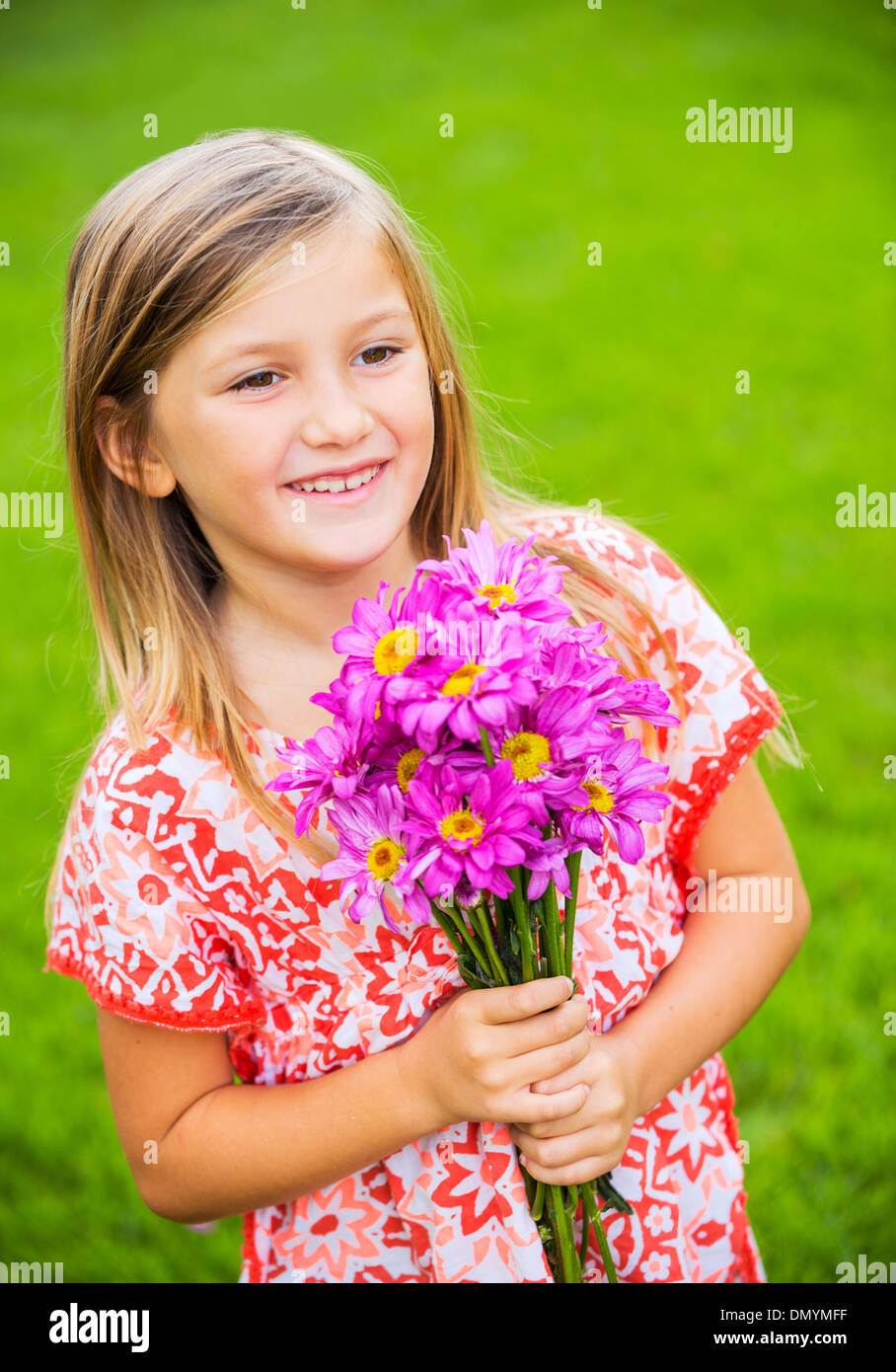 Portrait of a smiling cute little girl with flowers - Stock Image
