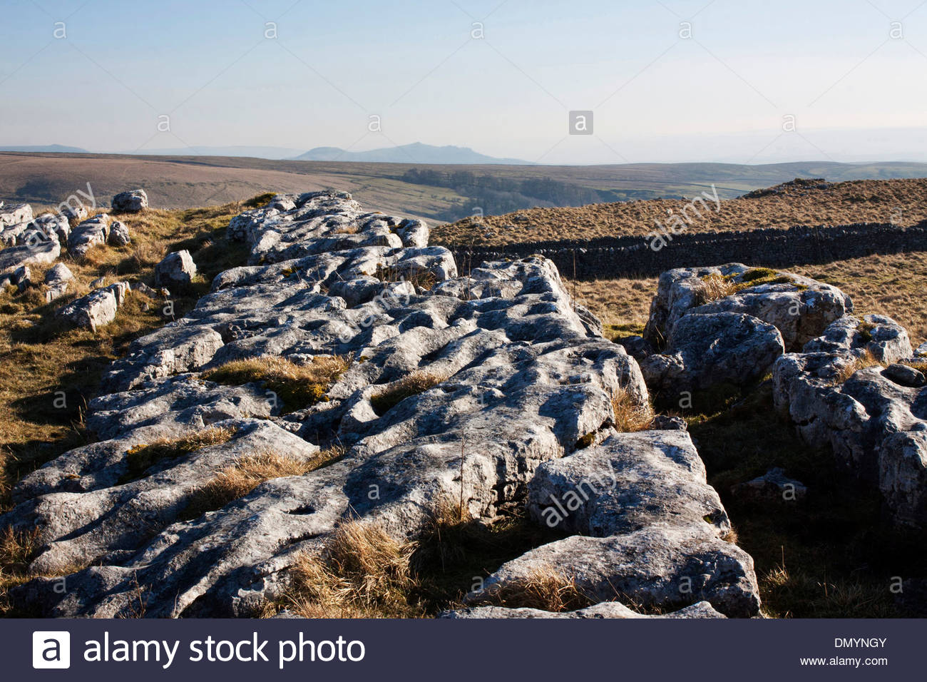 Near Malham in North Yorkshire, the sun illuminating and casting shodows on the the limestone pavements. - Stock Image