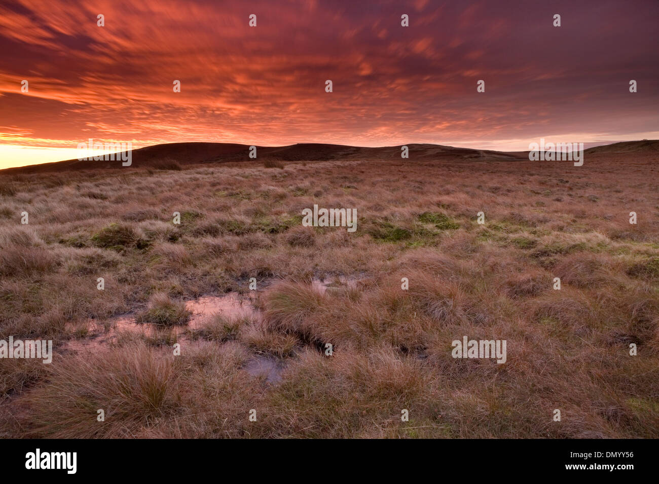 A vivid sunset makes the clouds red over the moorland of Goyt's Moss near Buxton Stock Photo