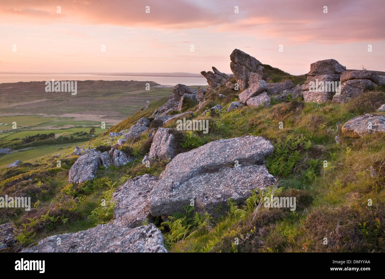 Boulders on the ridge of Rhossili Down near Llangennith, Gower Peninsula, overlook Rhossili Bay at sunset. - Stock Image