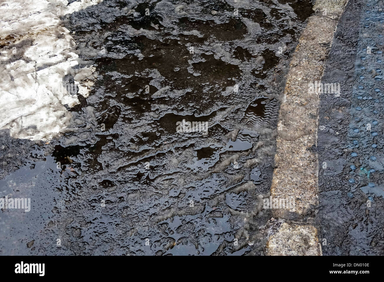 Slush and snow and an icy puddle in the street in New York City winter - Stock Image
