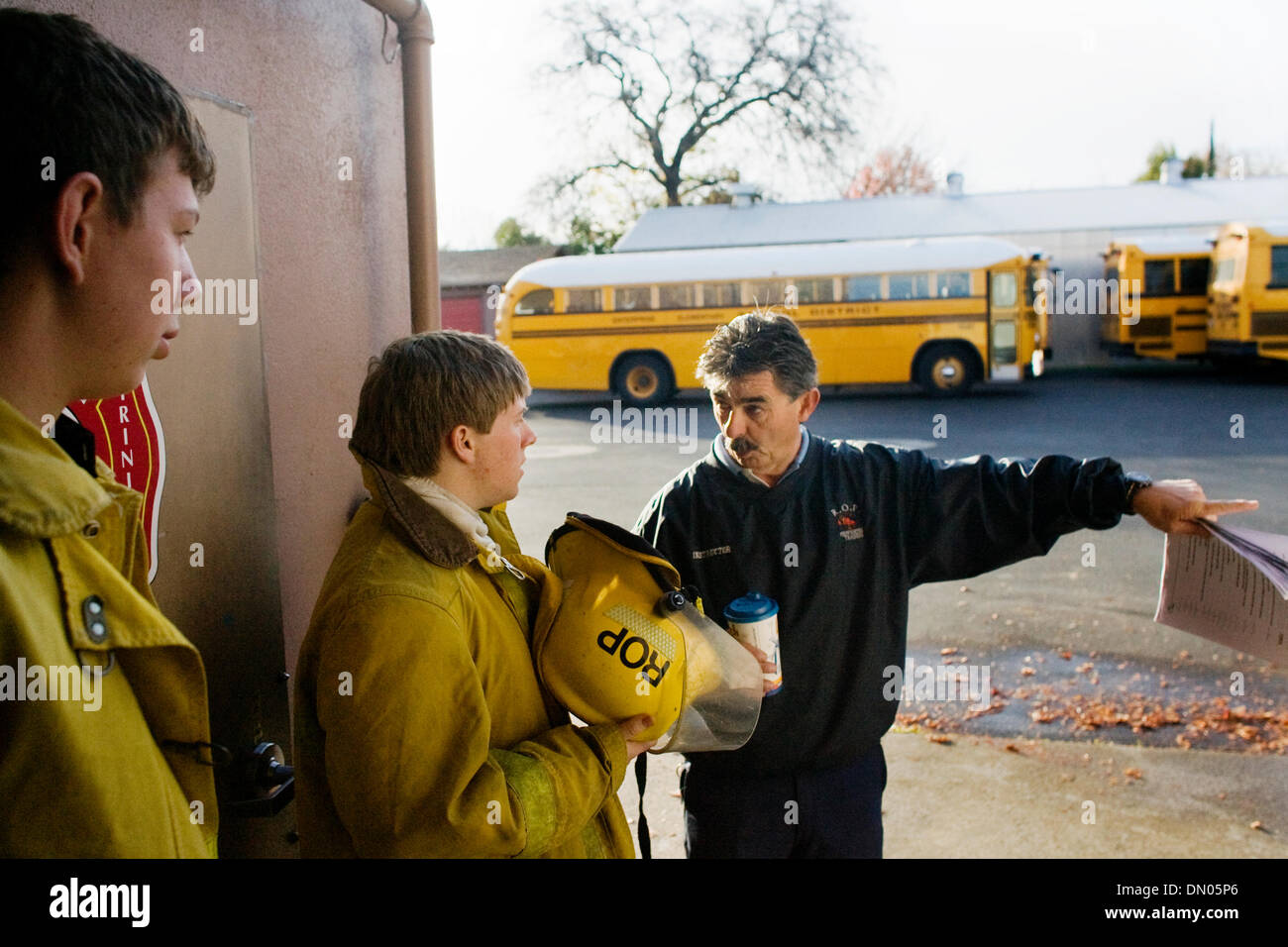 Dec. 04, 2009 - Redding, California, USA - Fire Chief Gary Lyon briefs students Lance Bechtoldt, 17, of West Valley High School, left, and William Bisso, 17, of Anderson High School, Friday during their firefighter training class at Redding Fire Department station No. 5. The training is part of the Shasta-Trinity Regional Occupational Program. The students will graduate and get the - Stock Image