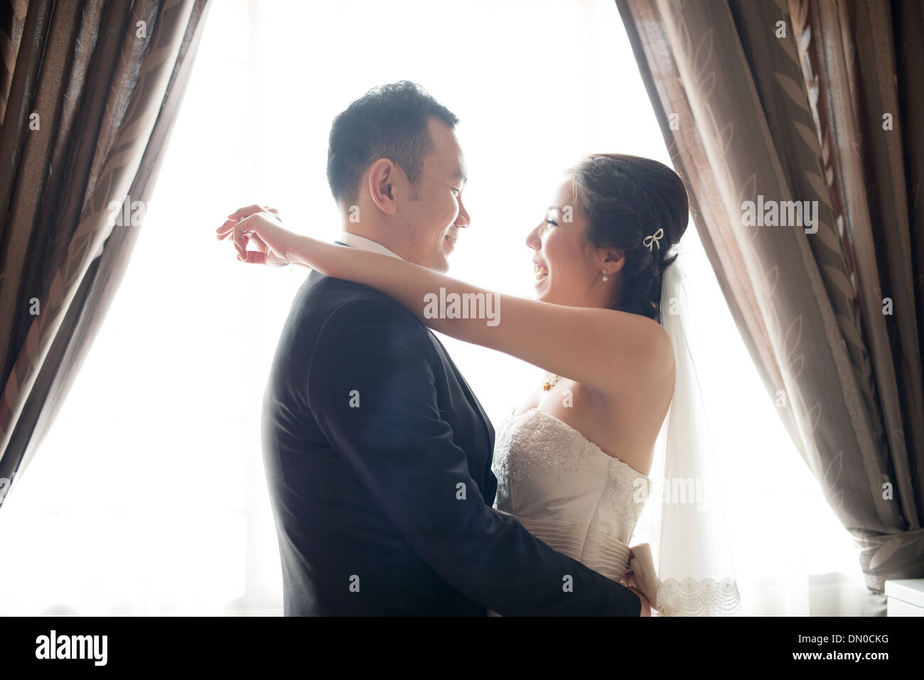 Romantic Asian Chinese wedding couple. Bride and groom dancing on wedding day. - Stock Image
