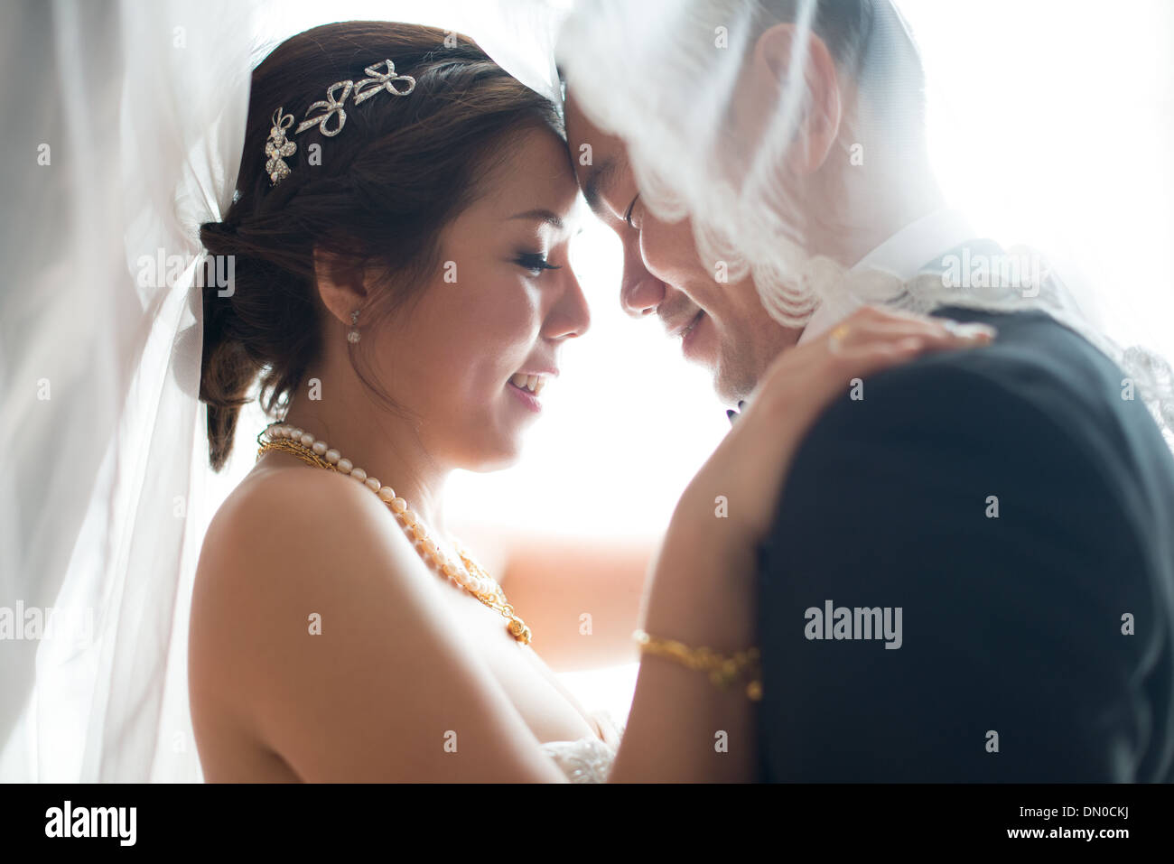Romantic Asian Chinese wedding couple. Bride and groom dancing in love on wedding day. - Stock Image