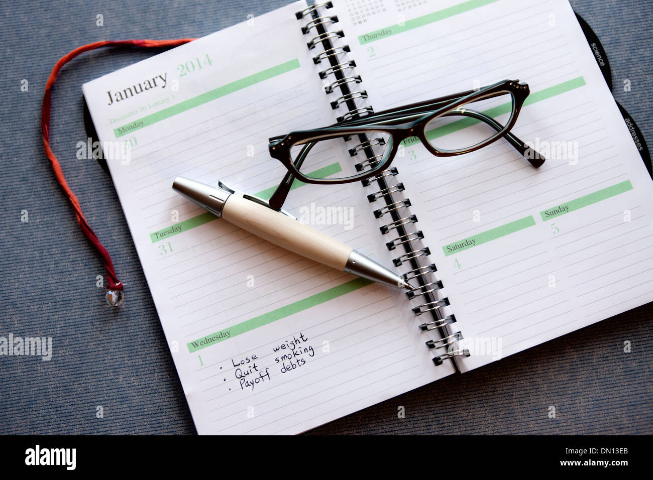 Making a New Year's Resolution in a day planner. - Stock Image