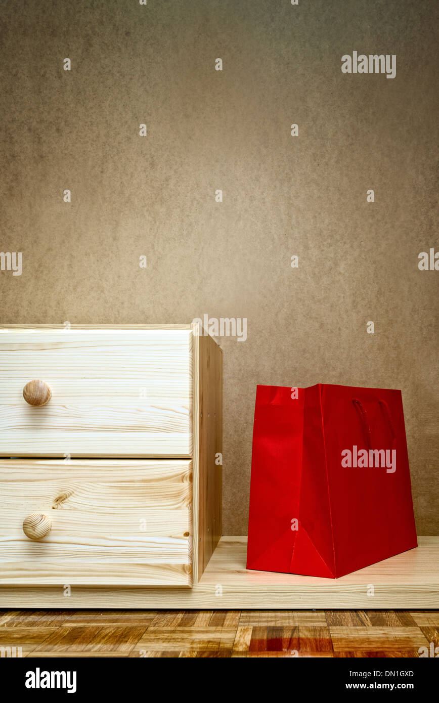 Red shopping bag in wooden beech cabinet. - Stock Image