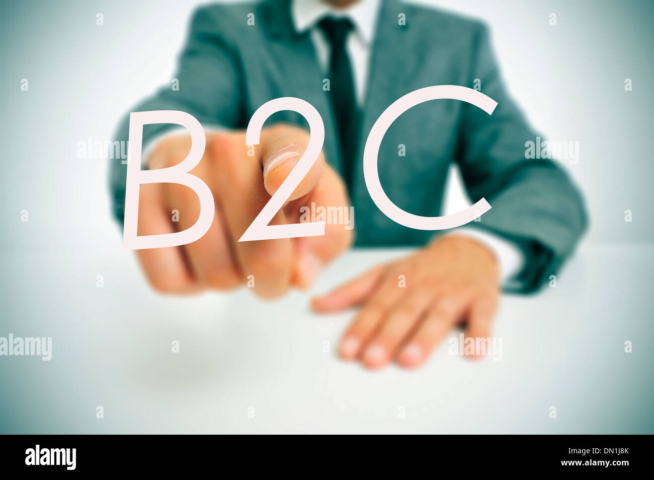 man wearing a suit sitting in a table pointing to the word B2C, business-to-consumer, written in the foreground - Stock Image