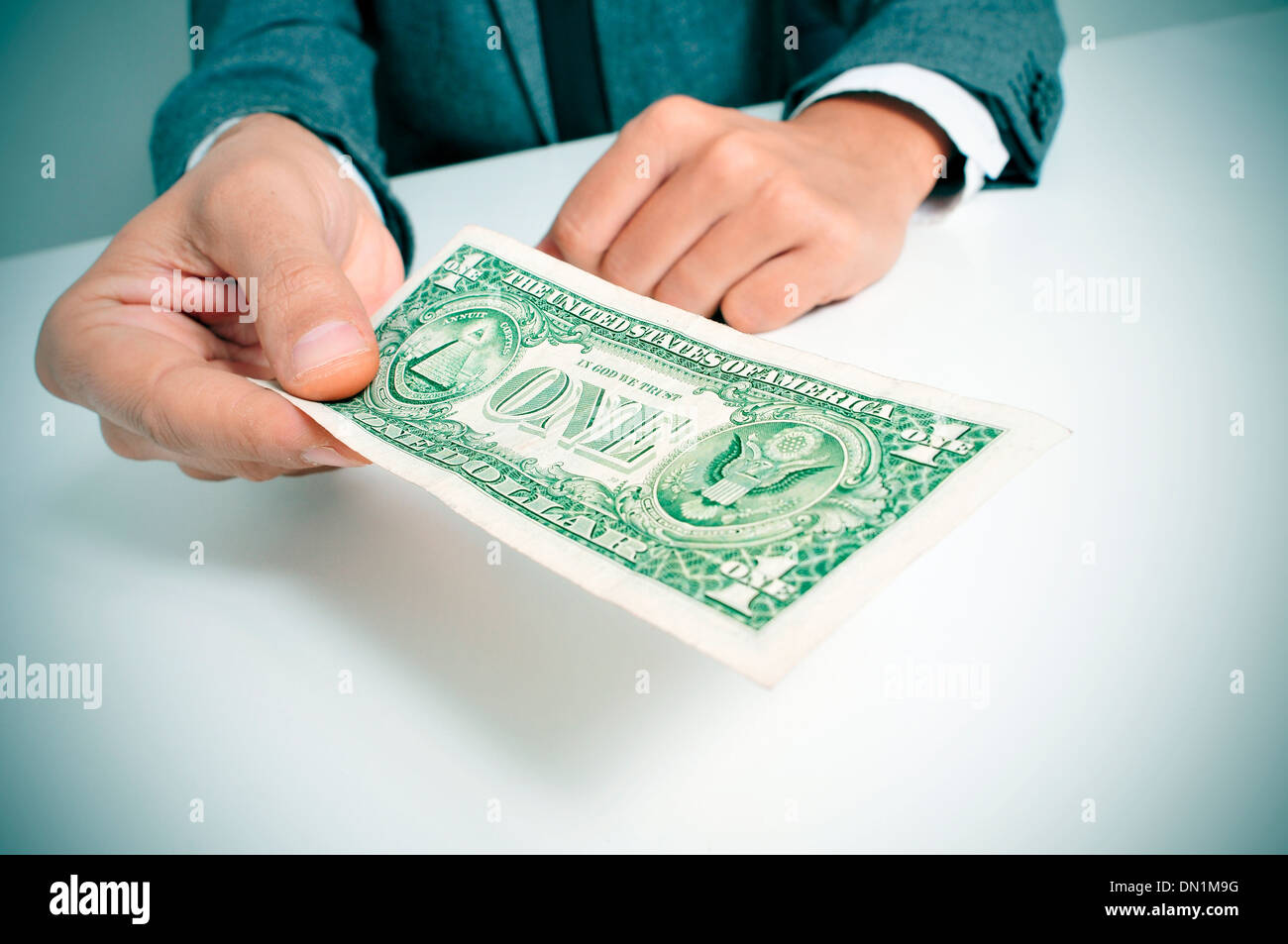 a man wearing a suit sitting in a desk offering a one US dollar bill Stock Photo