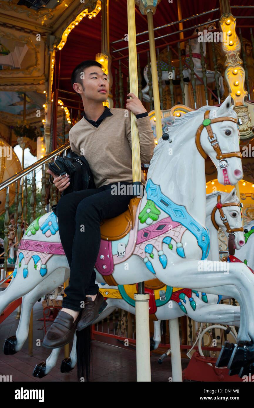 Paris, France, Young Chinese Man, on French Merry-go-Round, Mange, Stock Photo