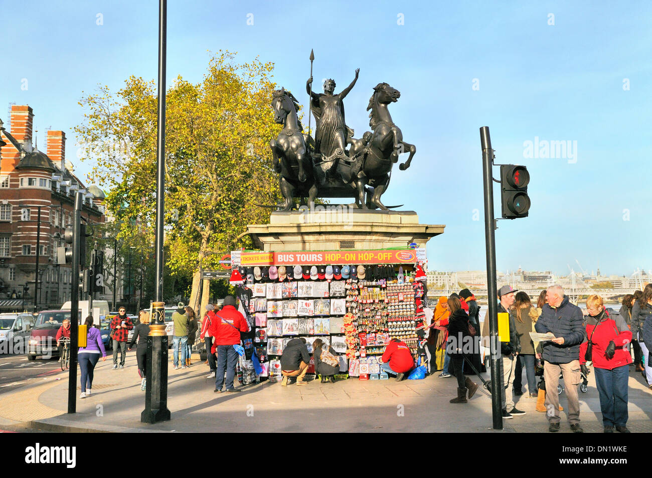Tourists browsing souvenir stall beneath the Chariot of Boadicea, Westminster, London, England, UK - Stock Image
