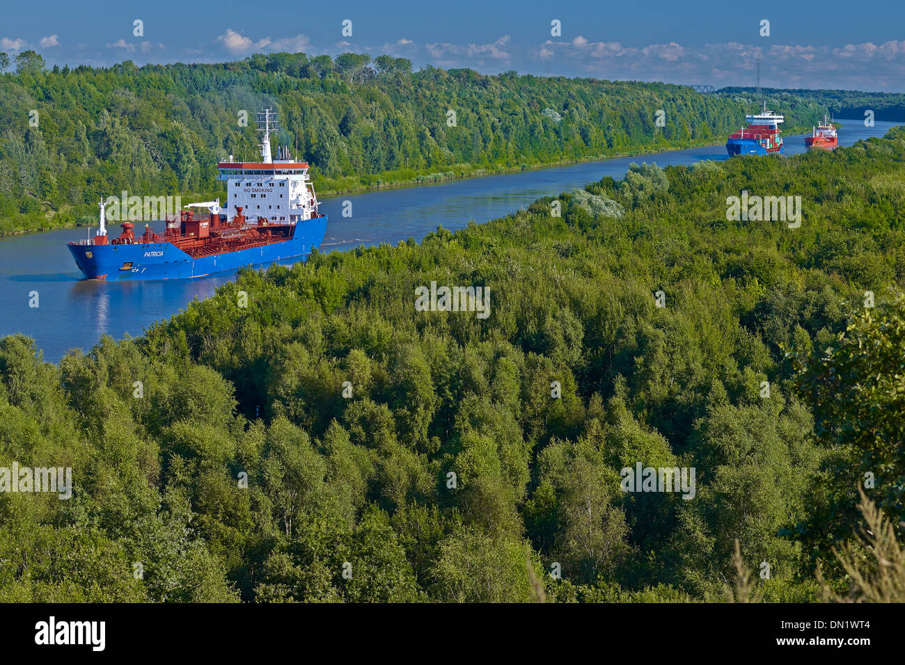 Tanker and container ships on the Kiel Canal near Itzehoe, Dithmarschen District, Schleswig-Holstein, Germany - Stock Image