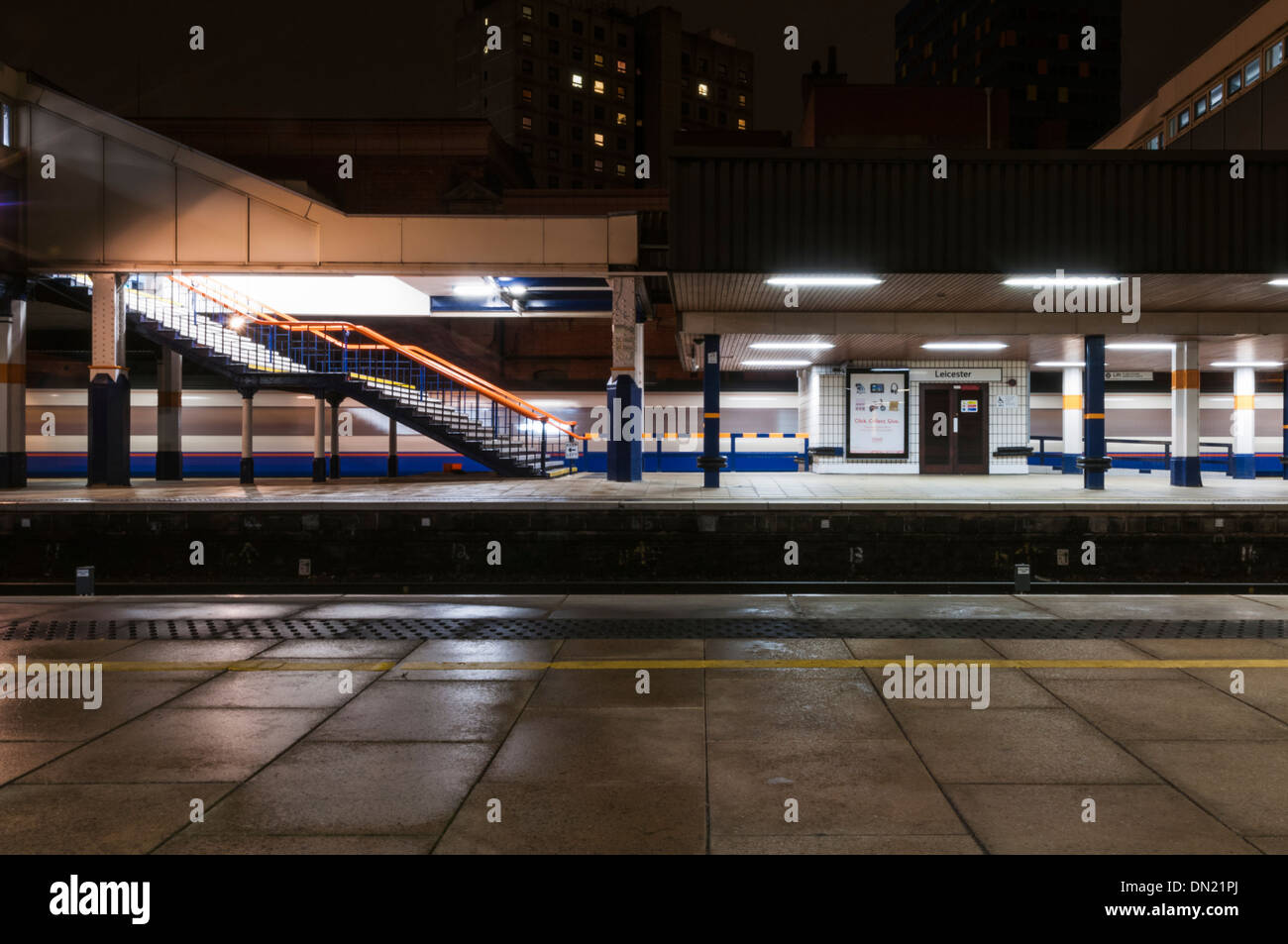 Long exposure of an East Midlands Trains passenger service passing through Leicester station at night. - Stock Image