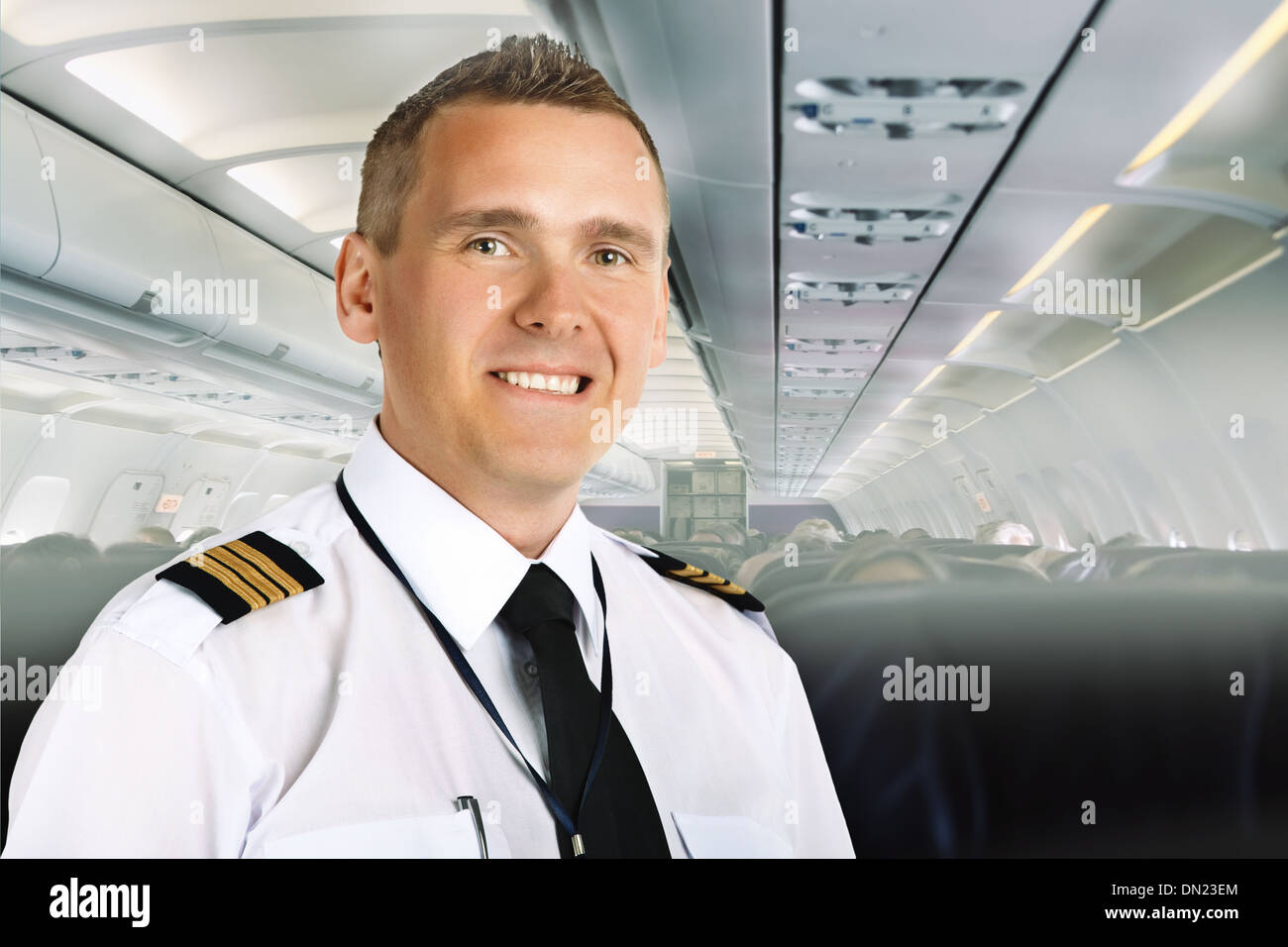 Airline pilot wearing uniform with epaulettes on board of passenger aircraft. - Stock Image