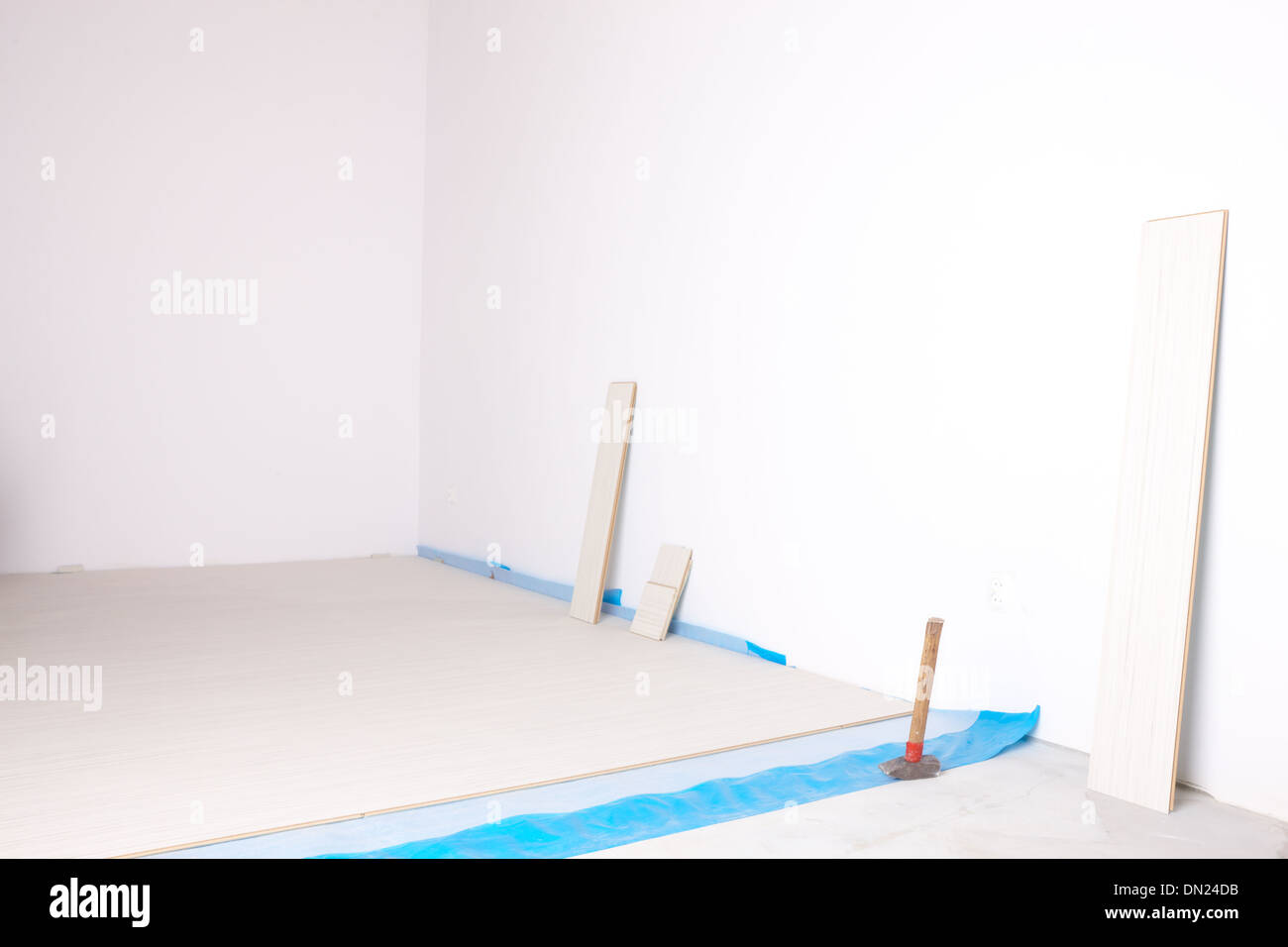 Empty room during renovation with laminated flooring, whithe walls and workers tools - Stock Image