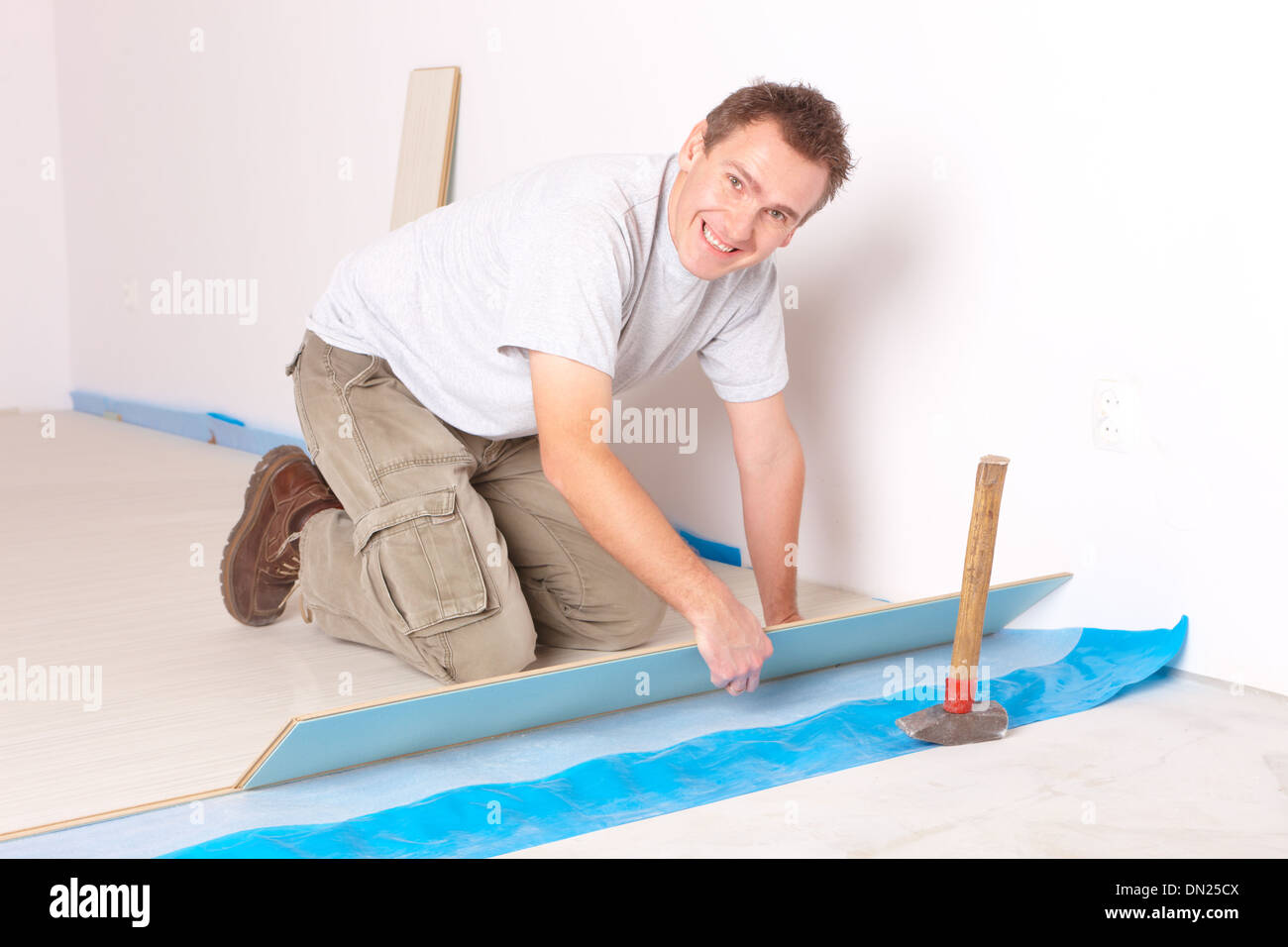 Happy manual worker installing a laminated flooring - Stock Image