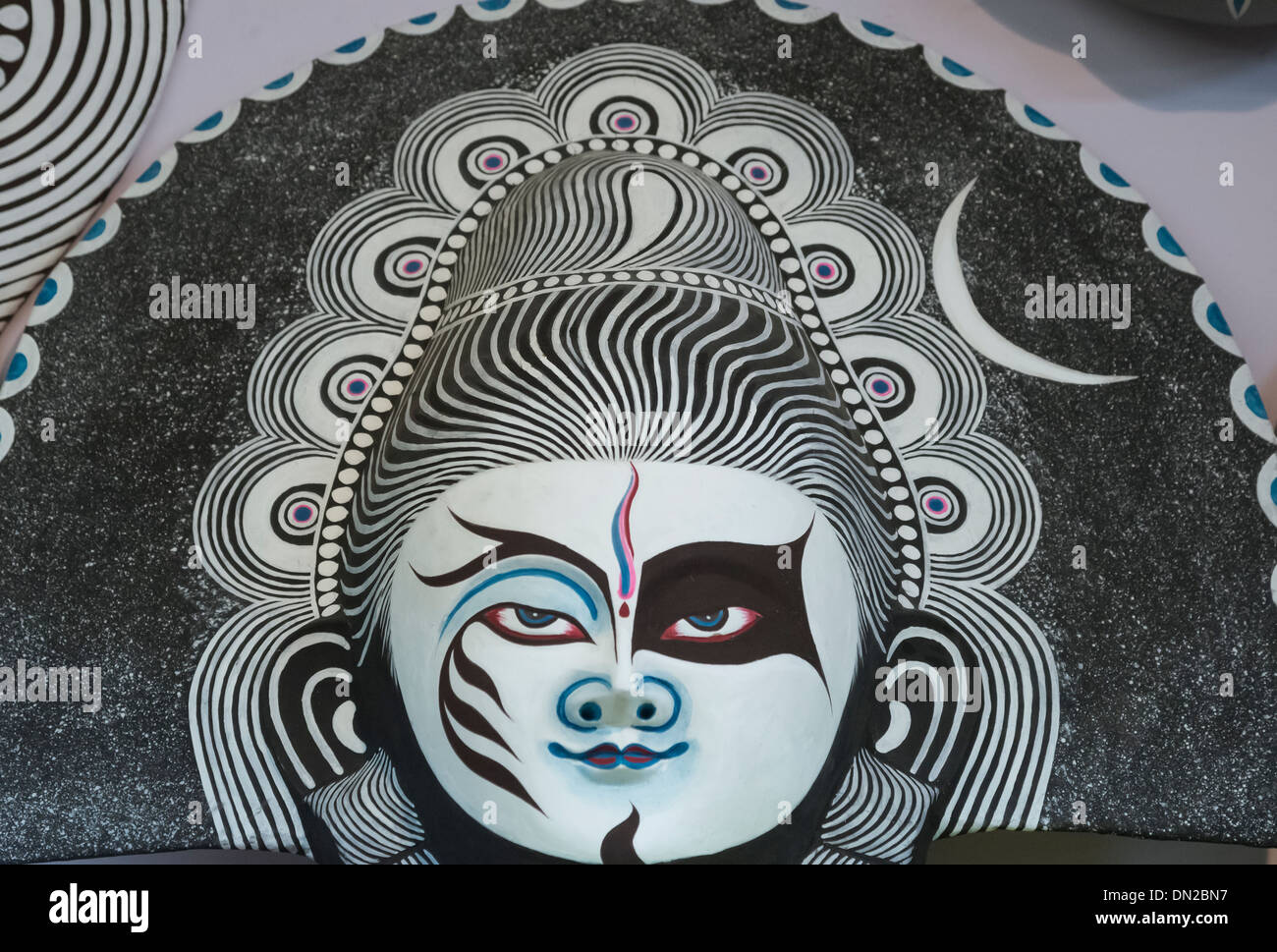 Handicraft of paper mask of Lord Shiva in colors of white and black,blue,pink indicating various qualities of the God. - Stock Image