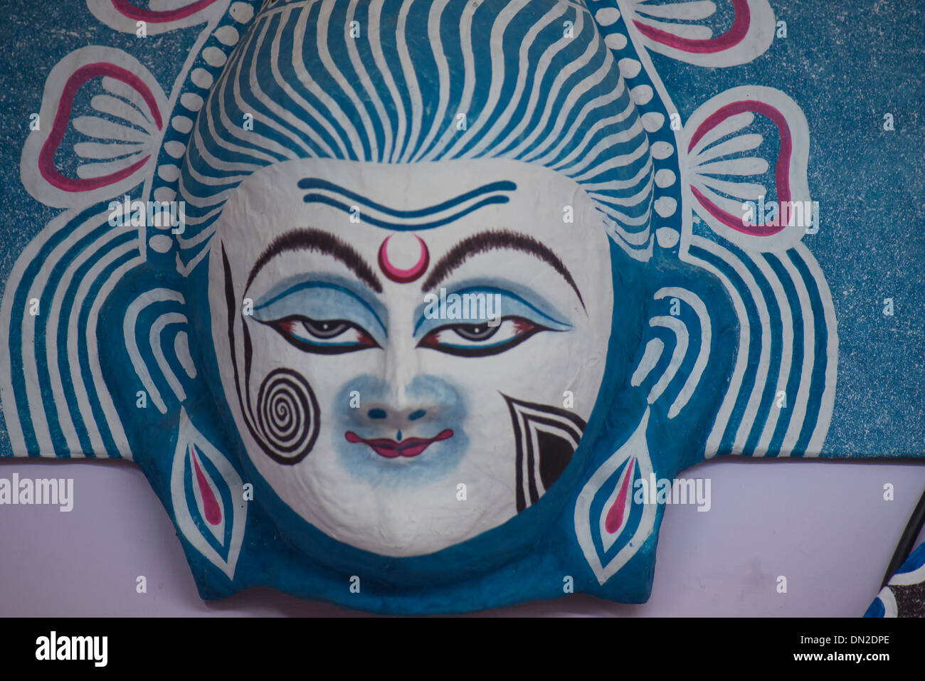Handicraft of paper mask of Lord Shiva in colors of white and black,blue, indicating benign grace of the God. - Stock Image