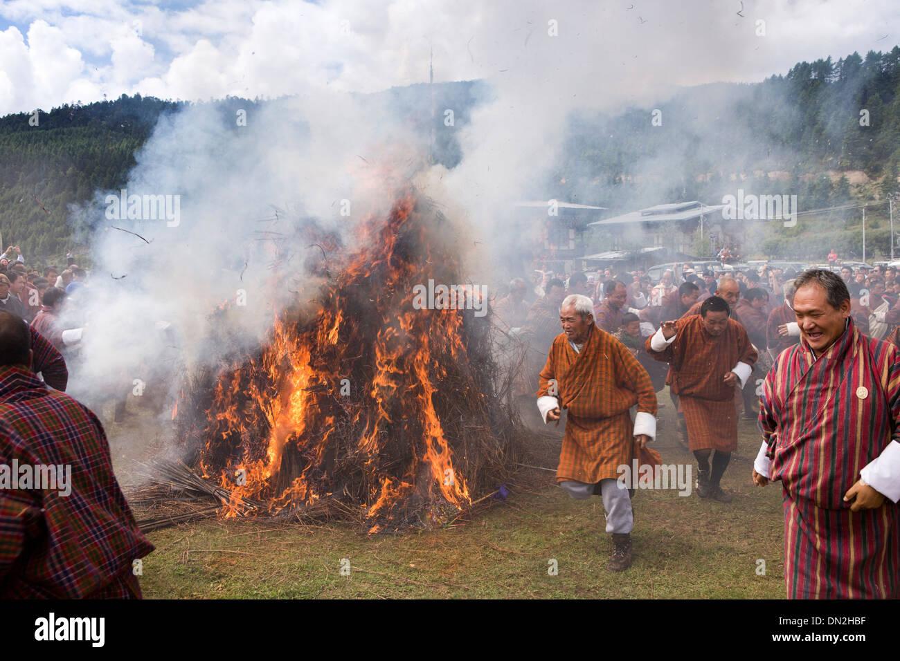 Bhutan, Thangbi Lhakang, Mewang, fire blessing ceremony, men running between fires - Stock Image
