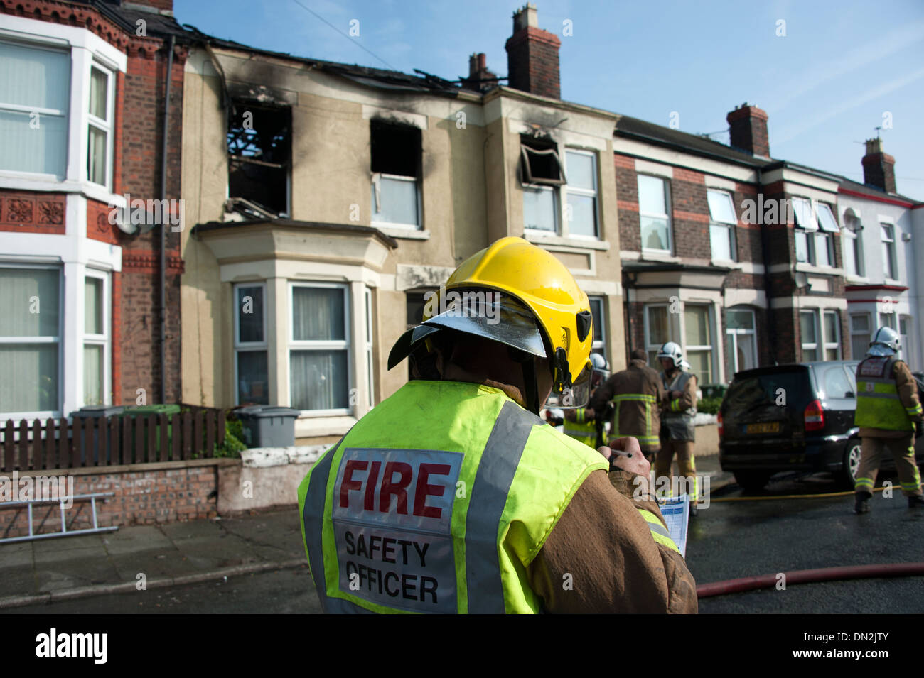 Fire Safety Officer outside burnt out house fire - Stock Image