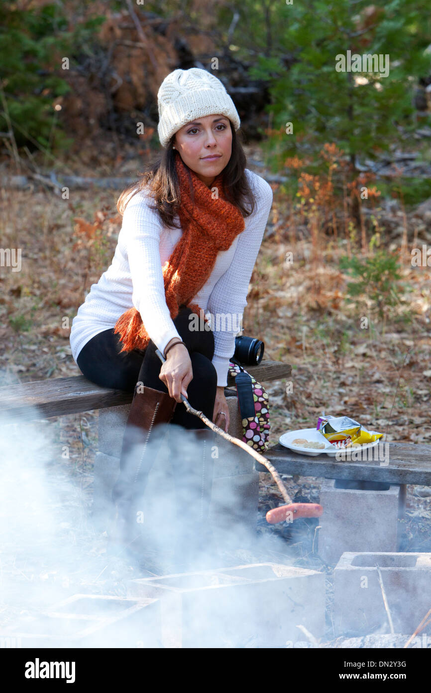Woman roasting a Hot Dog over a smoky fire Stock Photo