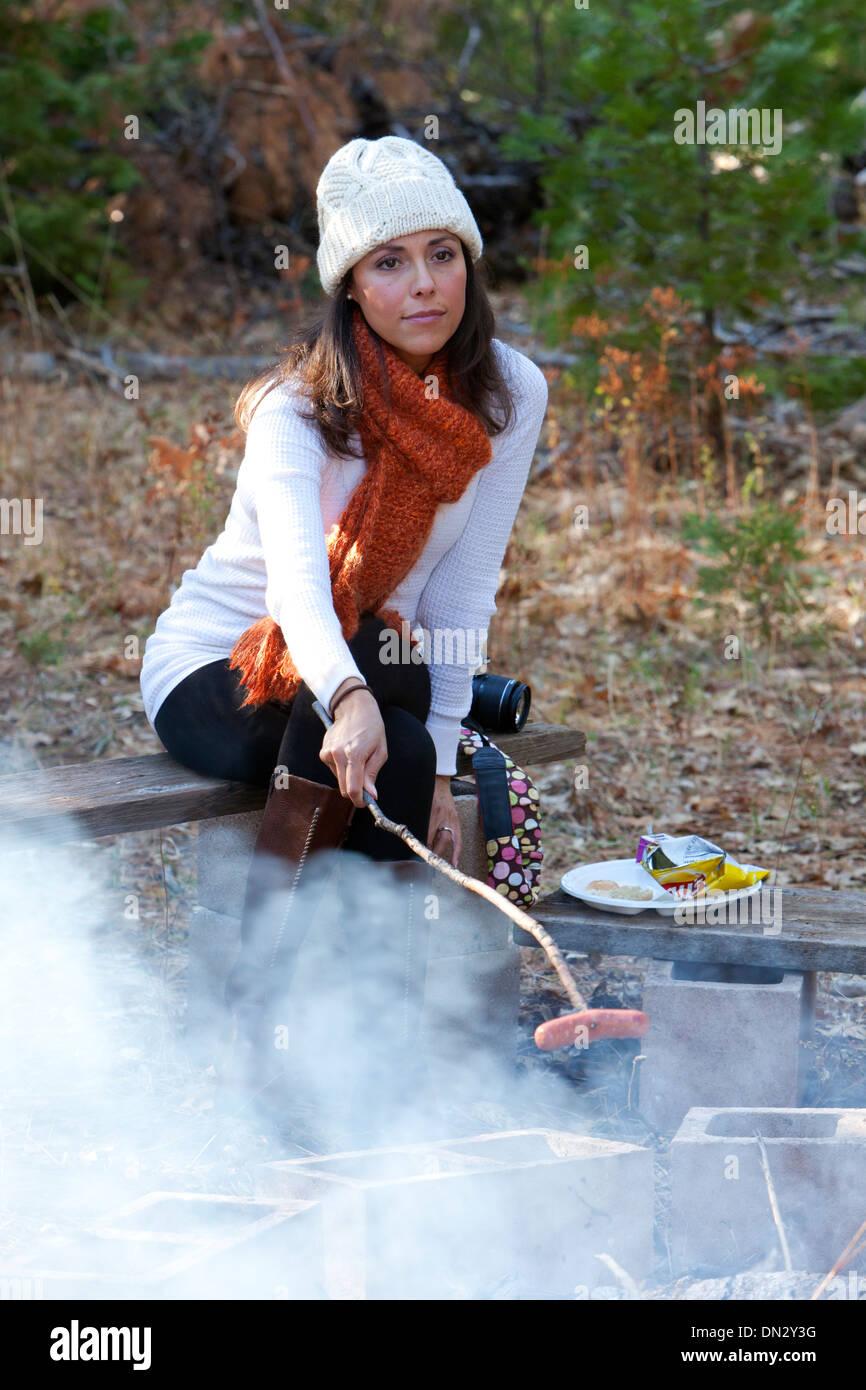 Woman roasting a Hot Dog over a smoky fireStock Photo