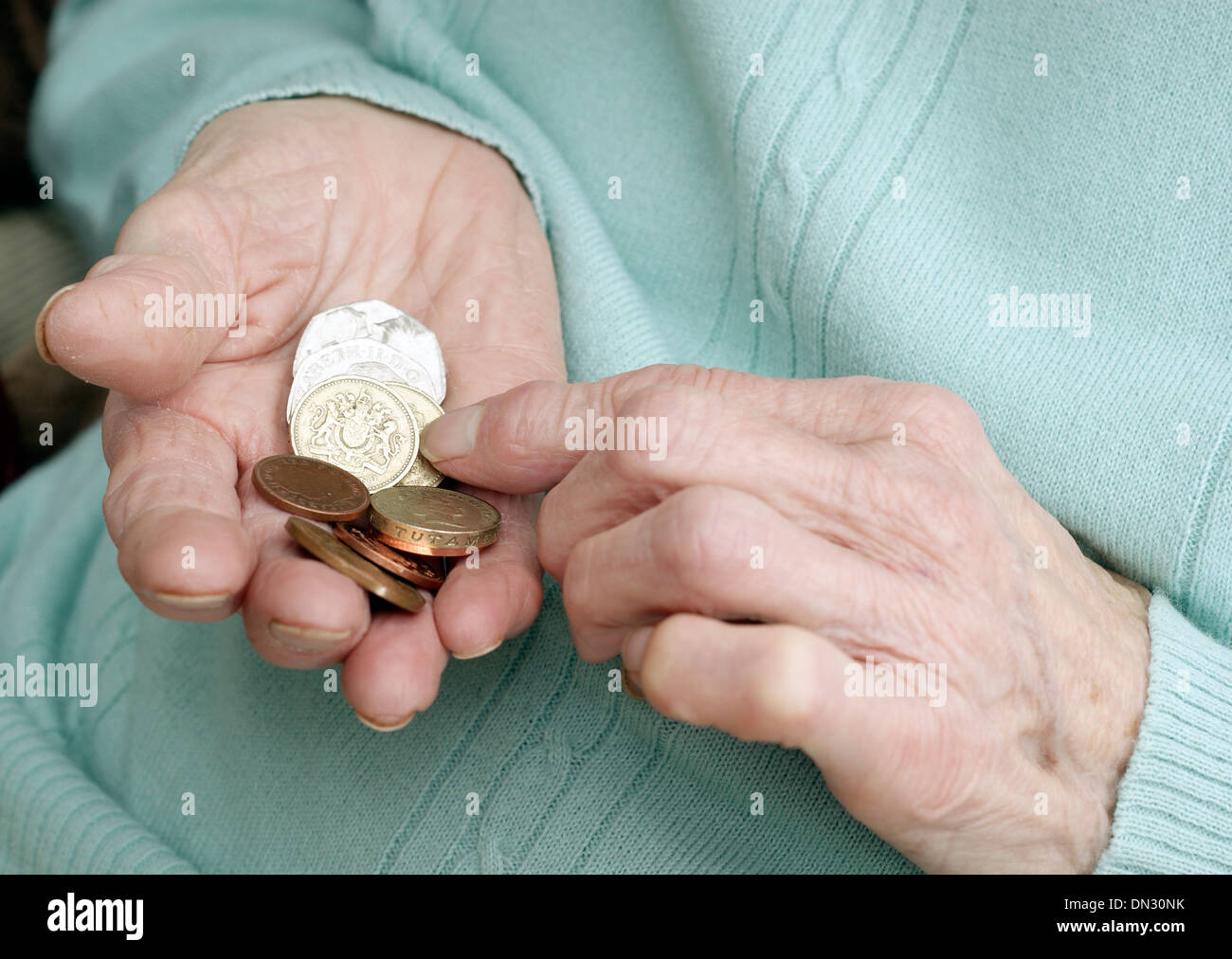 Elderly woman holding a mixture of coins (going through money in the age of austerity) - Stock Image