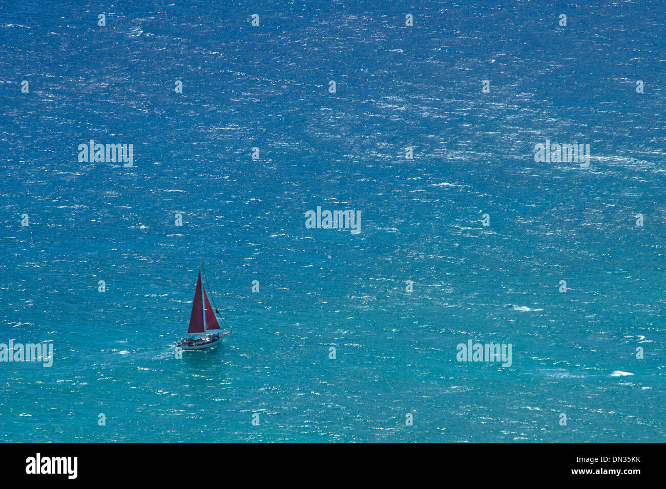 Small yacht sailing in open ocean - Stock Image