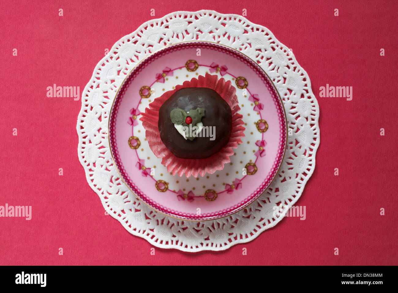 Christmas pudding chocolate truffle cake on pink decorative plate and doilie Stock Photo