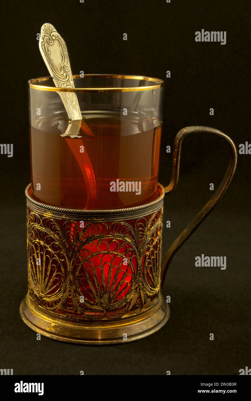 Glass with glass-holder, tea and a silver spoon on a black background. - Stock Image