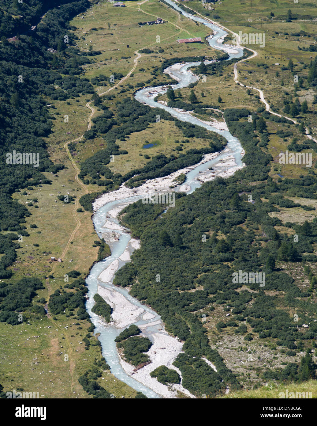 Areal view of a river with opaque glacier water and footpath on a green valley plain near  Gletsch in Swiss alps - Stock Image