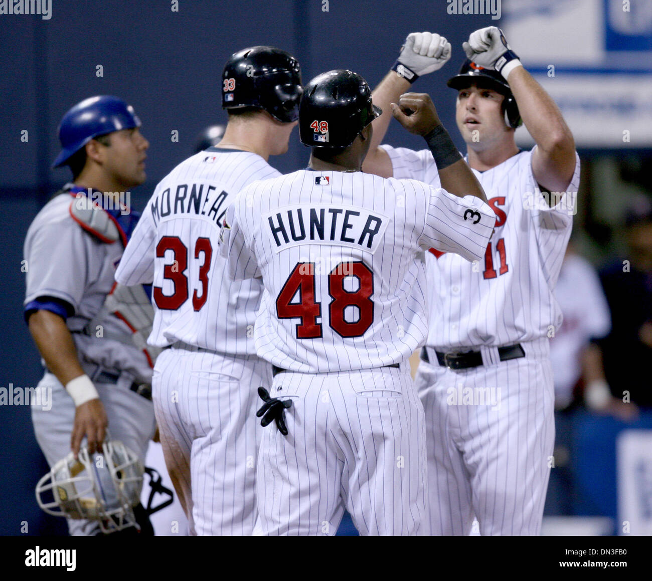 Jun 31, 2006; Minneapolis, MN, USA; Minnesota Twins' Josh Rabe (right) knocked a home run off the Texas Rangers' starter John Rheinecker to bring in Justin Morneau (left) and Torii Hunter (center) who congratulated him at the plate. The Twins defeated the Rangers 15-2 at the Metrodome in Minneapolis, Minnesota, Monday, July 31, 2006.  Mandatory Credit: Photo by Jeff Wheeler/Minneap Stock Photo