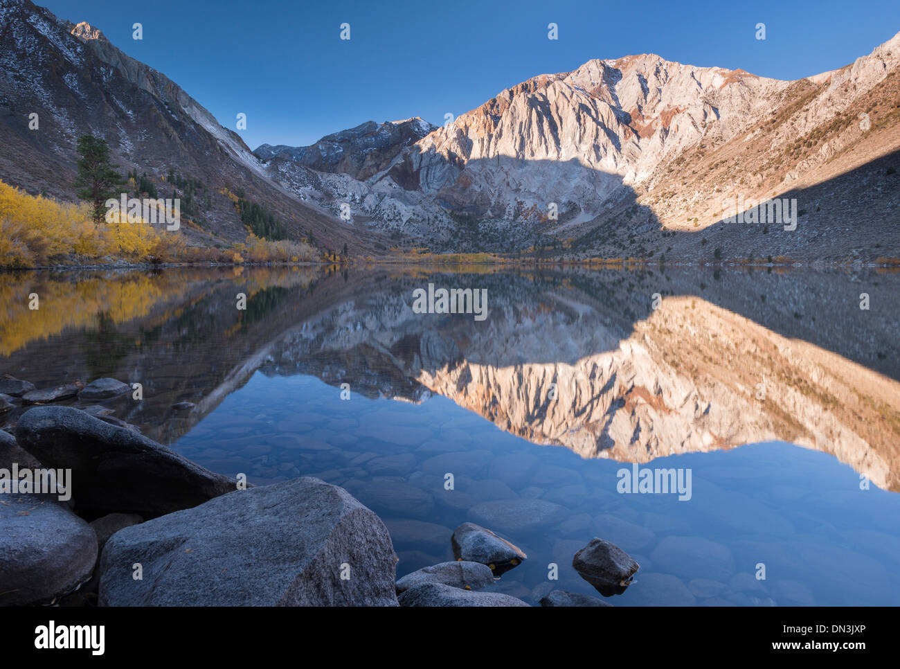 Early morning sunshine lights the Eastern Sierra Mountains beyond Convict Lake, California, USA. Autumn (October) 2013. - Stock Image