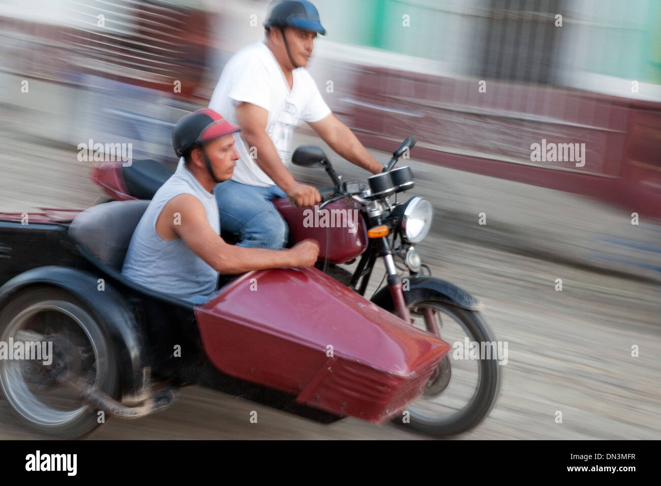 Cuba, men riding a motorcycle and side car with motion blur, Trinidad, Cuba Caribbean, Latin America - Stock Image