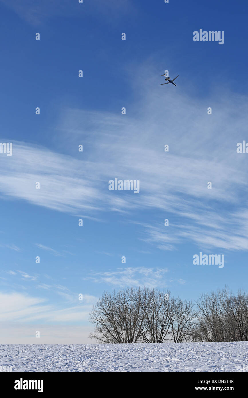 A jet airplane flying over a snowy field in Minnesota. Stock Photo