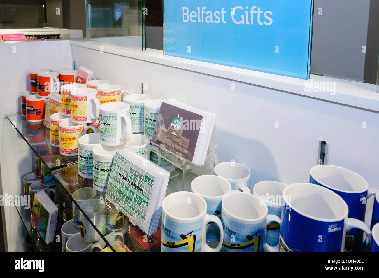 Mugs, coasters, pens and bags branded with 'Belfast' on sale in Visit Belfast tourist information centre - Stock Image