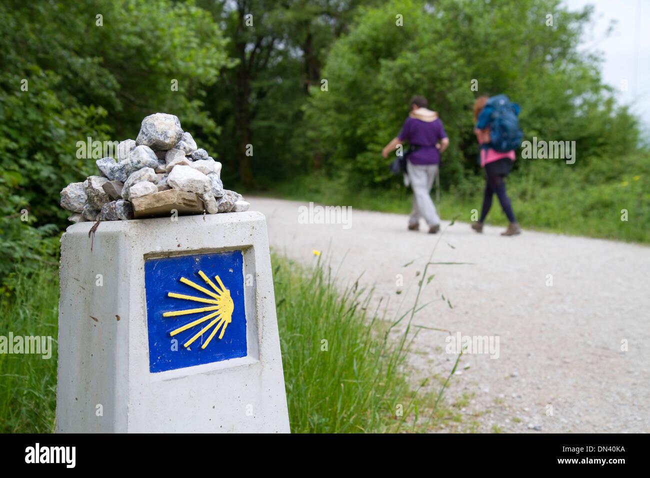 Pilgrims walk near a marker along the Camino De Santiago, the Way of St. James pilgrimage route, Navarra, Spain. - Stock Image