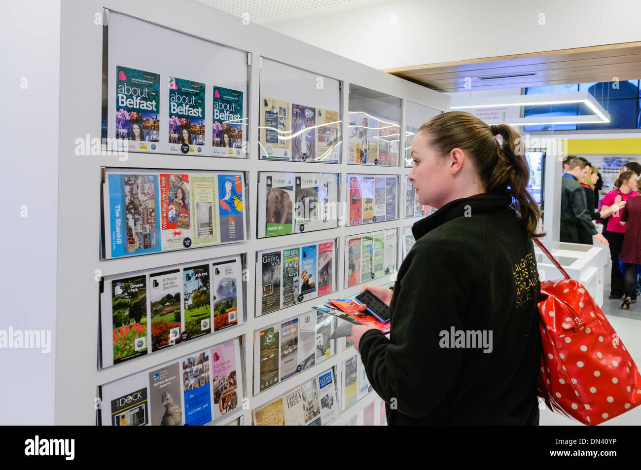 A woman browses the tourist information leaflets in Visit Belfast tourist information centre - Stock Image