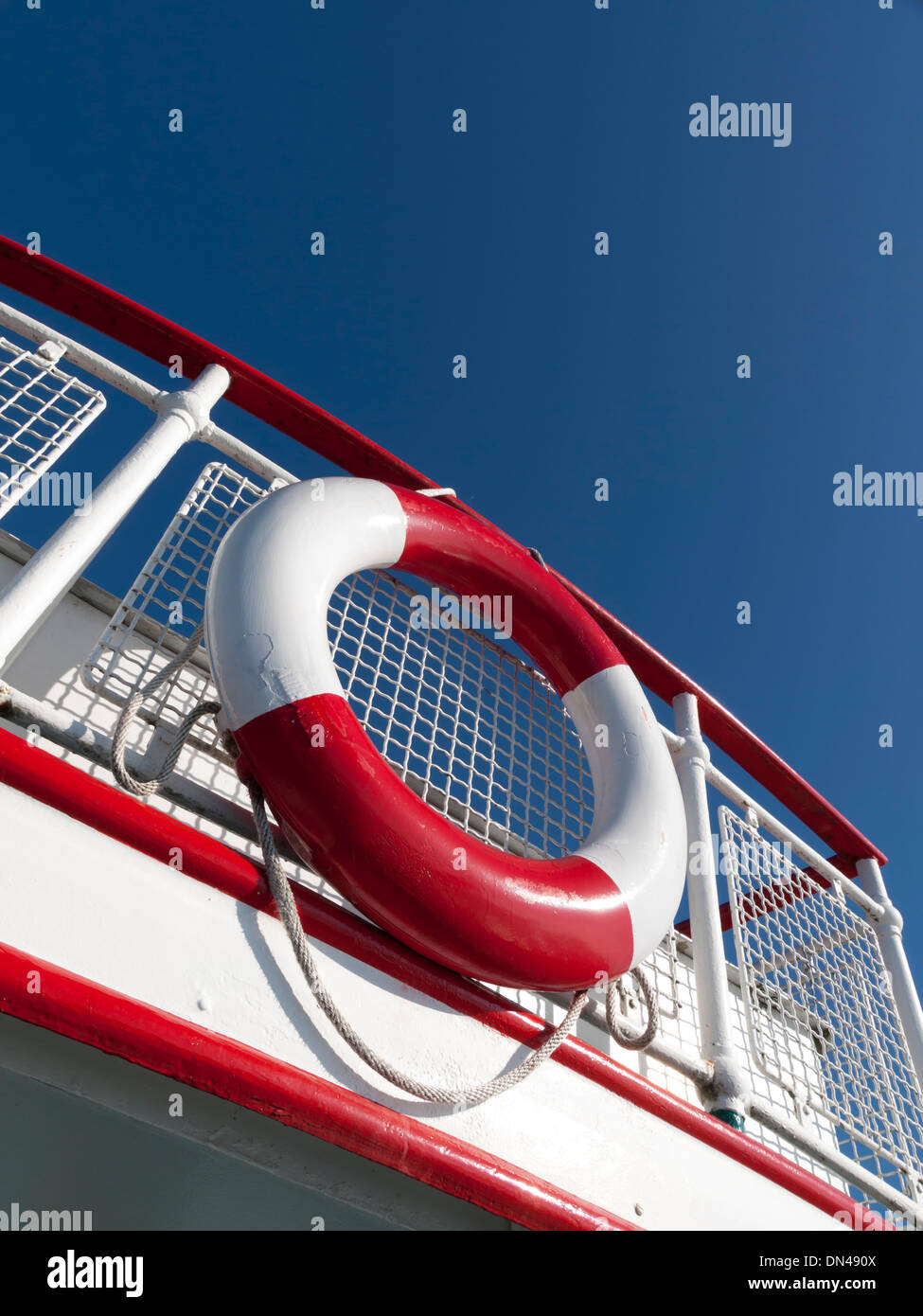 Bright red and white life-saver hanging off a boat's rail - Stock Image