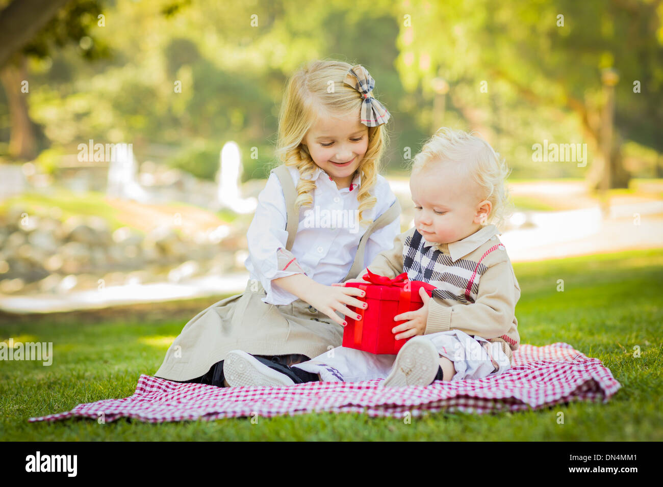 Sweet Little Girl Gives Her Baby Brother A Wrapped Gift on a Picnic Blanket Outdoors at the Park. - Stock Image
